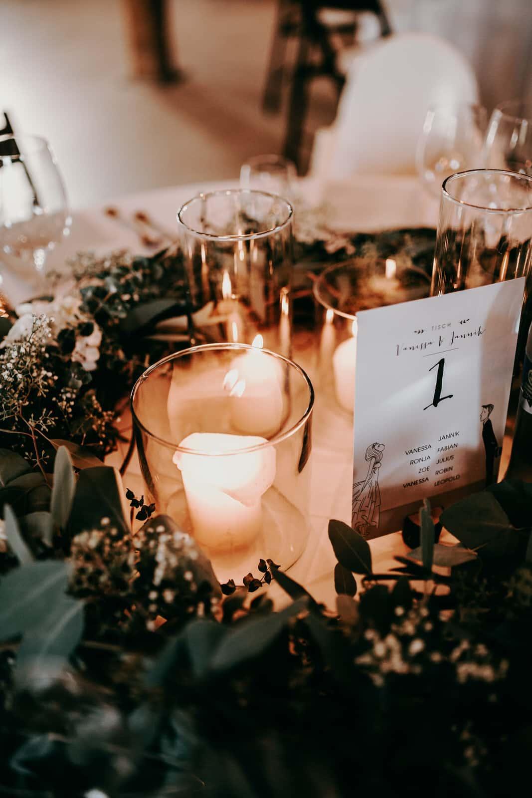 Als Hochzeitsfotografen lieben wir Details.Zu sehen ist ein Ausschnitt die Tischdekoration einer Hochzeitsfeier: weiße Stumpferen in einem edlen Glas, das Kerzenlicht flackert und gibt dem danebenliegenden Eukalyptus einen besonderen Farbton. Die Tischkarte zeigt die Tischnummer an und die Namen der Hochzeitsgäste, welche sich an diesem Tisch einfinden sollen.