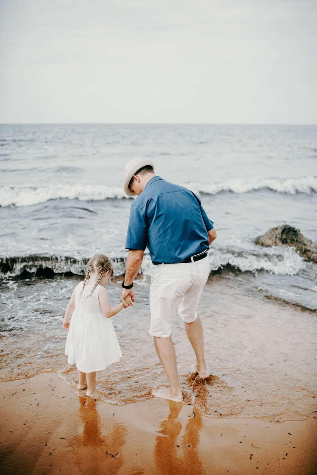 Als Hochzeitsfotograf auf Malta. Ein älterer männlicher Teilnehmer der Strandhochzeit läuft mit einem kleinen Kind an der Hand am Strand entlang. Sie sehen sich die Gischt der Wellen an. Auch das sind die wunderbaren Momente einer Hochzeit - wenn die Familie und Freunde zusammenkommen- und wir als Hochzeitsfotografen mittendrin!