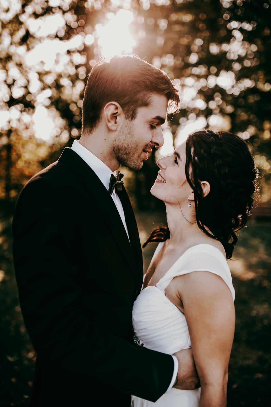 Als Hochzeitsfotografen lieben wir warmes natürliches Licht. SO wie hier auf diesem Bild. Es sind nur die Köpfe und ein Teil des Oberkörpers des Brautpaares zu sehen. Braut und Bräutigam sehen sich verliebt an.
