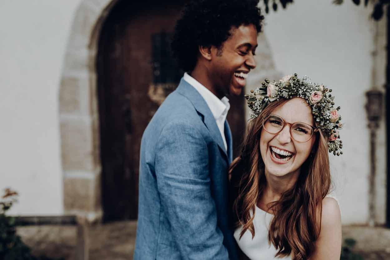 Als Hochzeitsfotograf an der Hochzeit von Melanie und Rob. Die Braut und der Bräutigam halten sich in den armen, während die Braut mit einem absolut authentischen Lachen in die Kamera lacht.